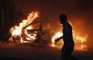A man looks at a car on fire at the site of a bomb attack in Baghdad